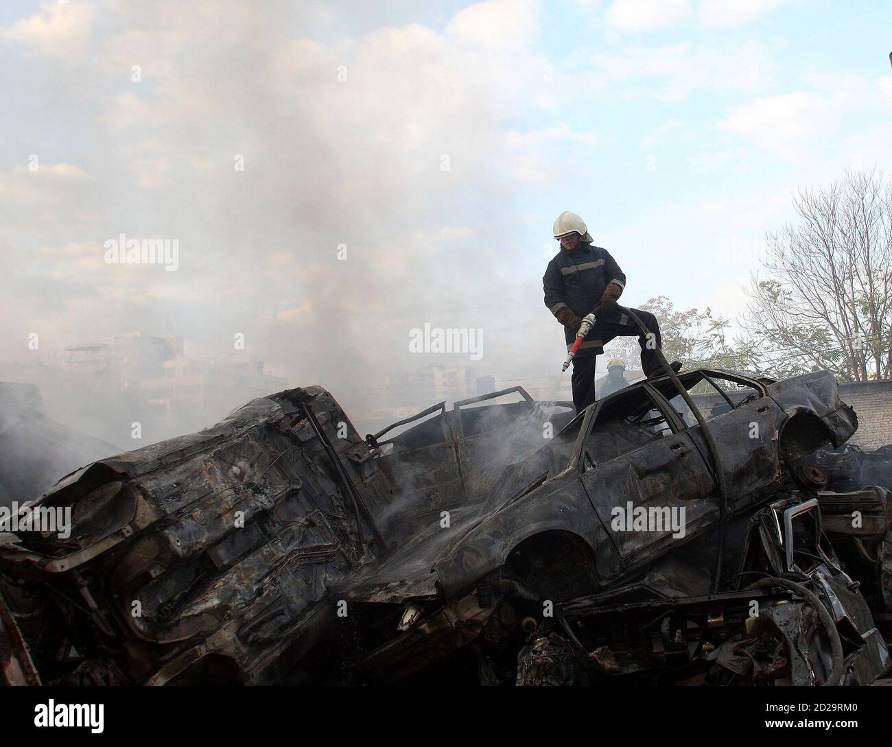 An Albanian firefighter tries to contain a fire at a used car yard in Tirana November 19, 2008.            REUTERS/Arben Celi (ALBANIA) Stock Photo