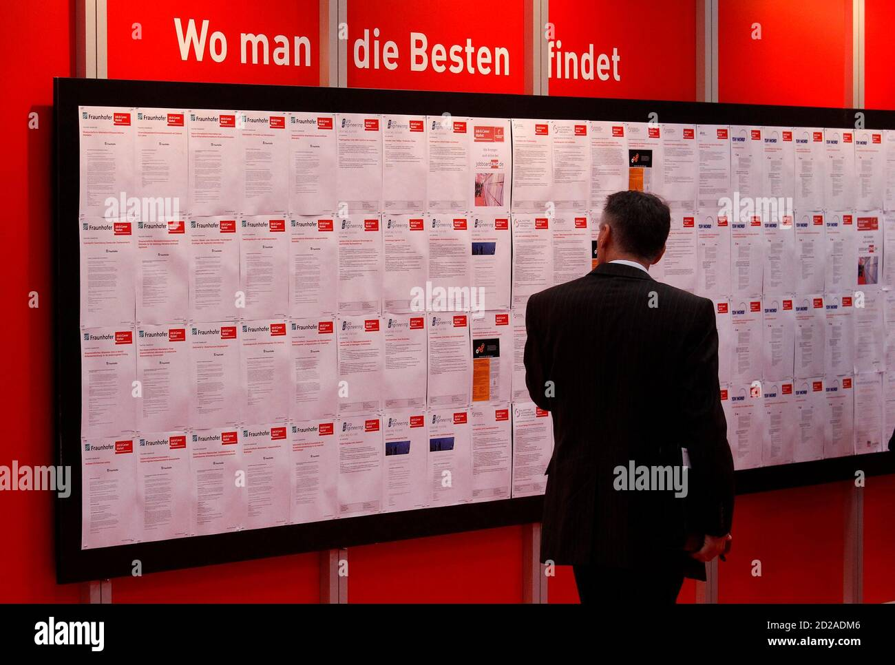 """A man read job offers during the first day of the """"Hannover Messe"""" industrial trade fair in Hanover April 19, 2010. The world's leading fair for industrial technology, with about 4,800 exhibitors from 63 nations, runs till April 23 with Italy as this year's partner country. The slogan reads: Where you can find the best!.     REUTERS/Tobias Schwarz     (GERMANY - Tags: SCI TECH) Stock Photo"""