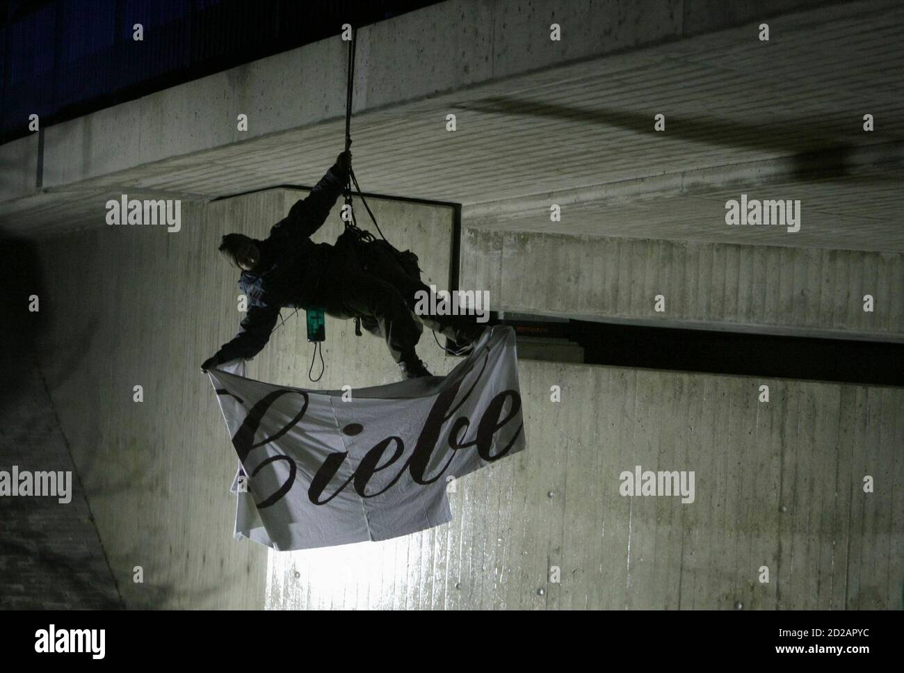 """An anti-nuclear activist from the German environmental organisation Robin Wood holds a banner reading """"Love"""", while hanging from a rope over a railway track in Oldendorf, between Lueneburg and Dannenberg November November 10, 2008. The controversial shipment of eleven Castor containers with spent German nuclear fuel arrived in Dannenberg on Monday and will be loaded onto trucks before transportation to the nearby Gorleben intermediate storage facility in northern Germany after it left the French reprocessing plant of La Hague on Friday.  REUTERS/Christian Charisius (GERMANY) Stock Photo"""