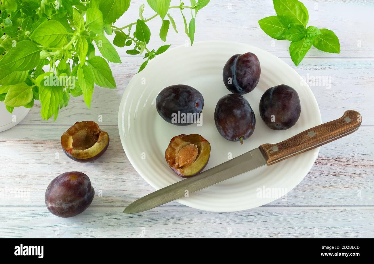 Ripe fresh plums and knife with a wooden handle on a white plate and kitchen herbs on painted wood surface Stock Photo