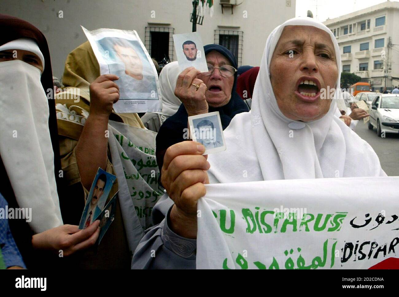 Algerian mothers hold up photographs of their disappeared loved ones during a protest outside the office of a human rights group in Algiers September 28, 2005. For a decade, dozens of mothers have held sit-ins once a week outside the office demanding the return of their loved ones or information about their fates. Algeria's national referendum, which will be held on September 29 aims at ending more than a decade of conflict which will help Islamists reach their goal of forming a purist Islamic republic ,an influential former leading militant said on Monday. REUTERS/Louafi Larbi Stock Photo