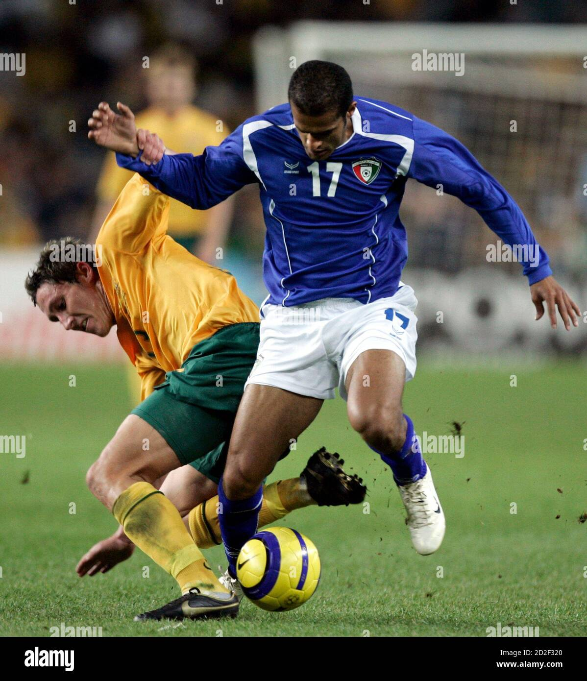 Australia's Mark Milligan (L) and Kuwait's Bader Al Mutwa challenges for the ball during their Asian Cup soccer qualifying match in Sydney August 16, 2006.  REUTERS/Will Burgess   (AUSTRALIA) Stock Photo