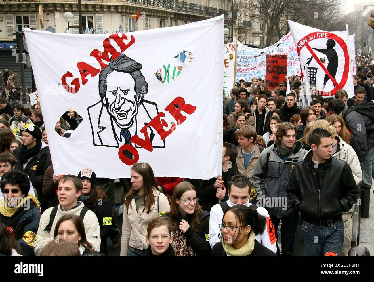 French students shout slogans as they carry a banner with the caricature of France's Prime Minister Dominique de Villepin during a protest march demanding the government to scrap a contentious youth jobs law in Paris March 23, 2006. Stock Photo