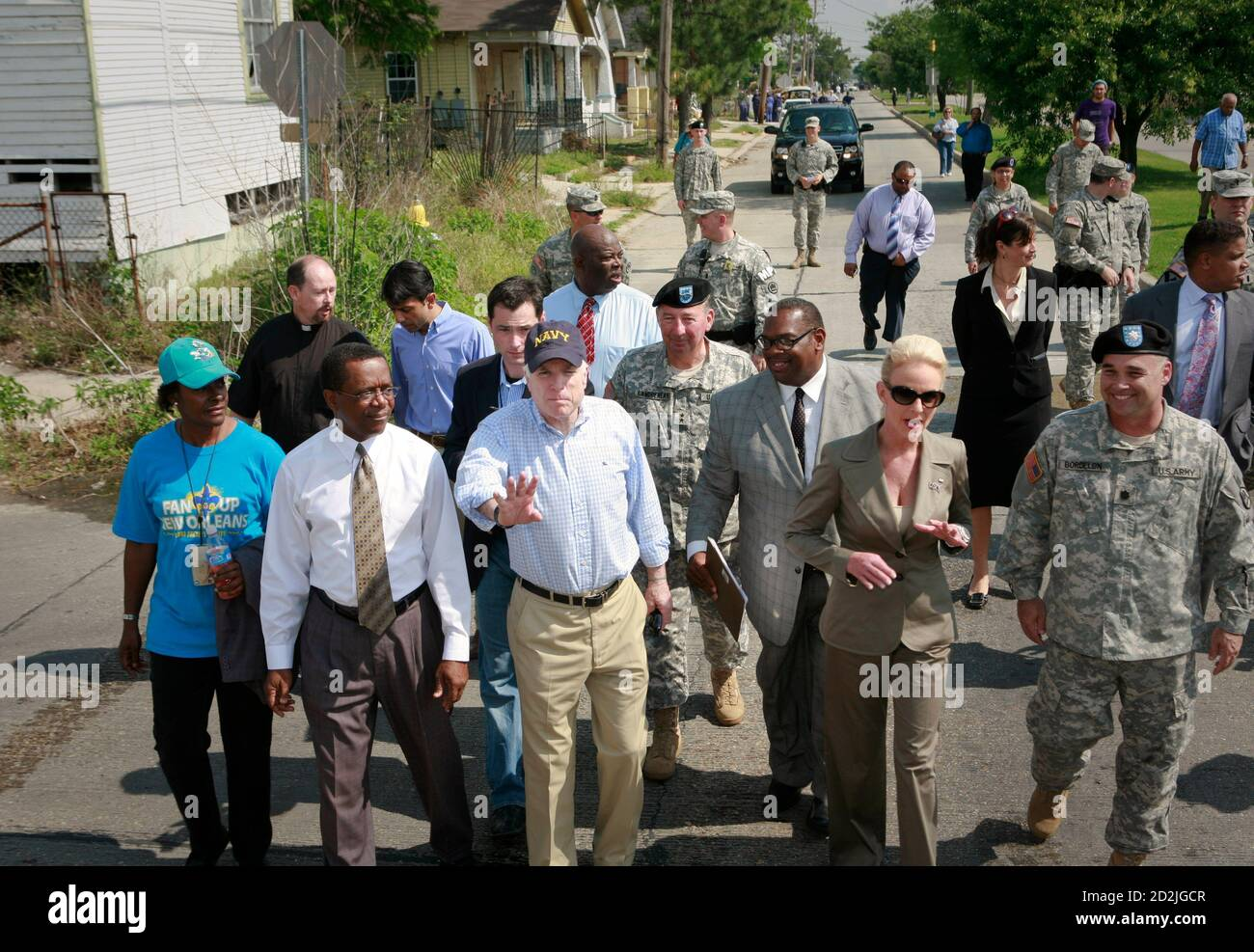 US Republican presidential candidate Senator John McCain (R-AZ) (front 3rd L) gestures for trucks carrying press members to move as his wife, Cindy (2nd R), talks to a national guardsman during a walking tour of the Lower Ninth Ward of New Orleans, Louisiana April 24, 2008. REUTERS/Lee Celano (UNITED STATES)  US PRESIDENTIAL ELECTION CAMPAIGN 2008 (USA) Stock Photo