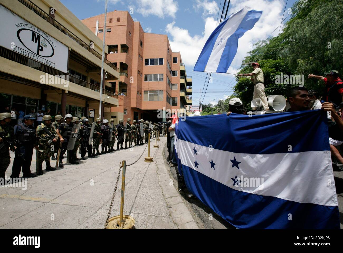 Supporters (R) of Honduras' ousted President Manuel Zelaya protest in front of the Public Ministry building in Tegucigalpa July 7, 2009. Ousted Honduran President Manuel Zelaya said on Tuesday he accepted the mediation of Costa Rican President Oscar Arias to try to solve his country's political crisis following the June 28 coup that ousted him. REUTERS/Oswaldo Rivas (HONDURAS POLITICS CONFLICT MILITARY) Stock Photo