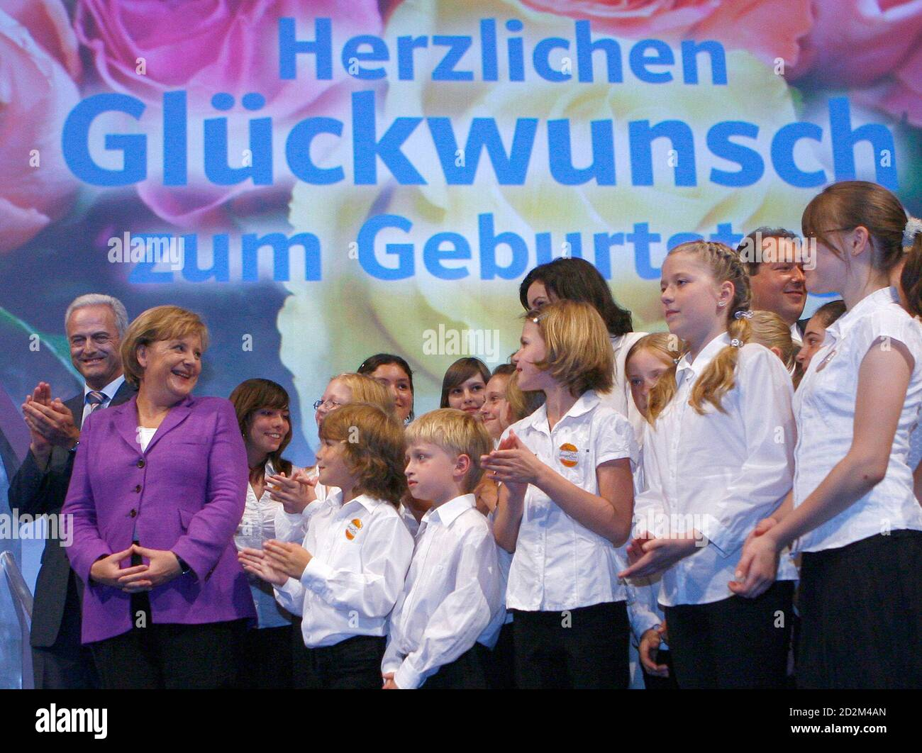 German Chancellor Angela Merkel (2ndL) smiles after she was sung a birthday  song by a childrens choir for her 55th birthday, at the start of a two-day  party meeting of Bavaria's Christian