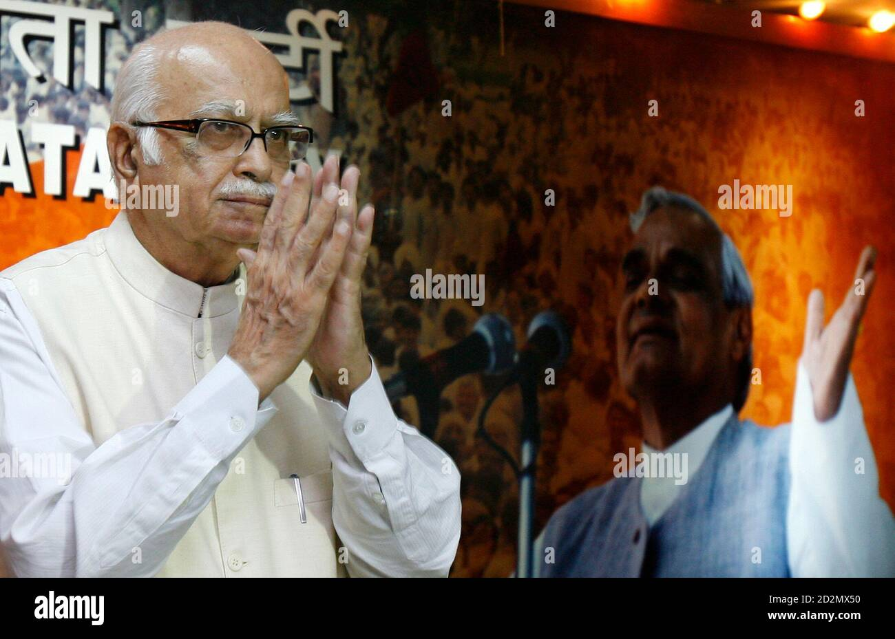 India's main opposition Bharatiya Janata Party (BJP) leader Lal Krishna Advani gestures during a news conference at his party's headquarters in New Delhi July 23, 2008. In the background is a picture of former Indian Prime Minister Atal Behari Vajpayee.   REUTERS/Vijay Mathur (INDIA) Stock Photo