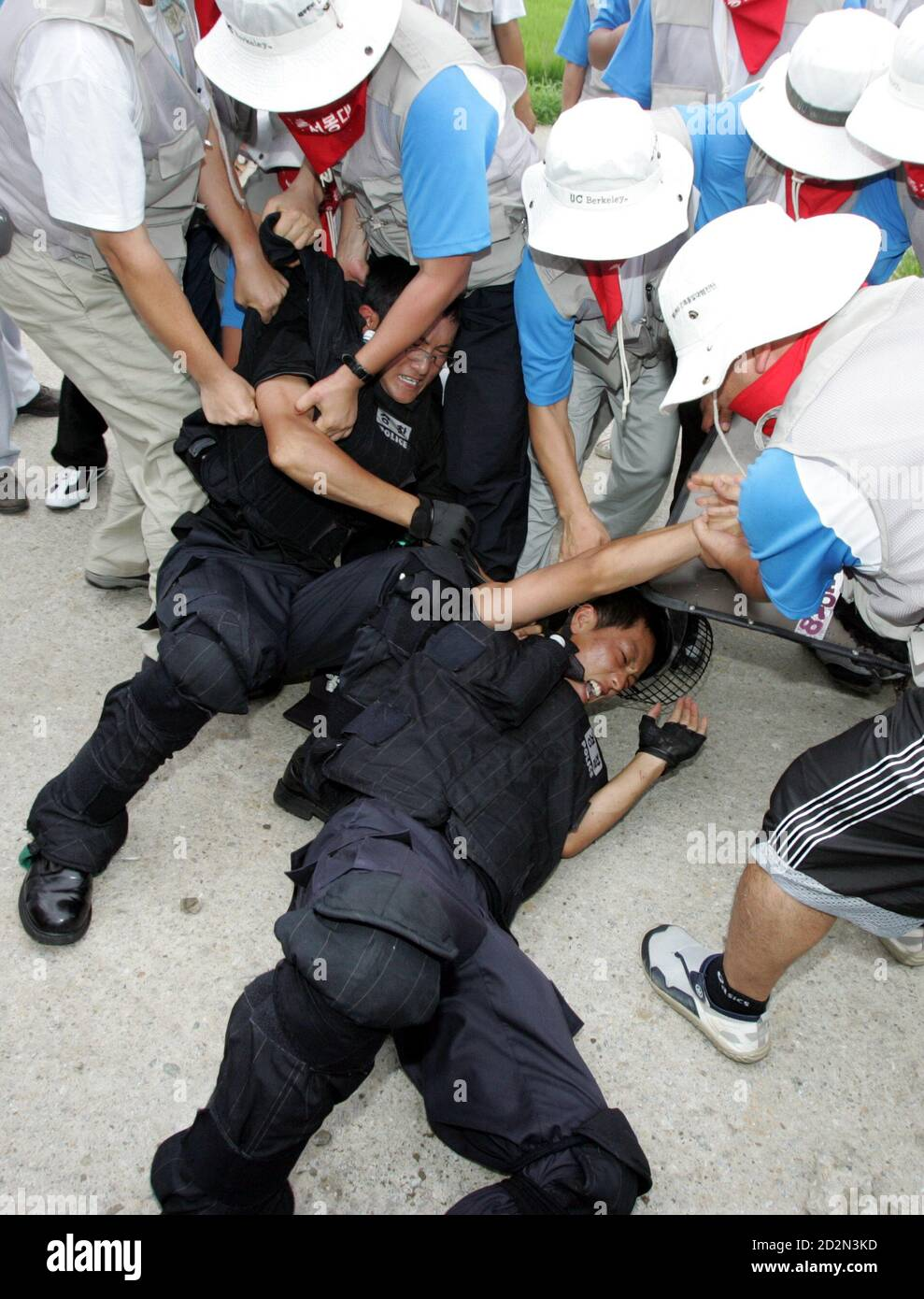 Protesters detain two riot policemen as police use shields and clubs to stop protesters trying to enter U.S. army's Camp Humphreys in Pyongtaek, South Korea.  Protesters detain two riot policemen as police use shields and clubs to stop the protesters trying to enter the U.S. army's Camp Humphreys in Pyongtaek, about 80 km (50 miles) south of Seoul, August 8, 2005. About 500 South Korean protesters from labour unions and college students' groups rallied near the U.S. army base on Monday as they demanded U.S. forces leave the country, which they insist block the reunification of the two Koreas.  Stock Photo