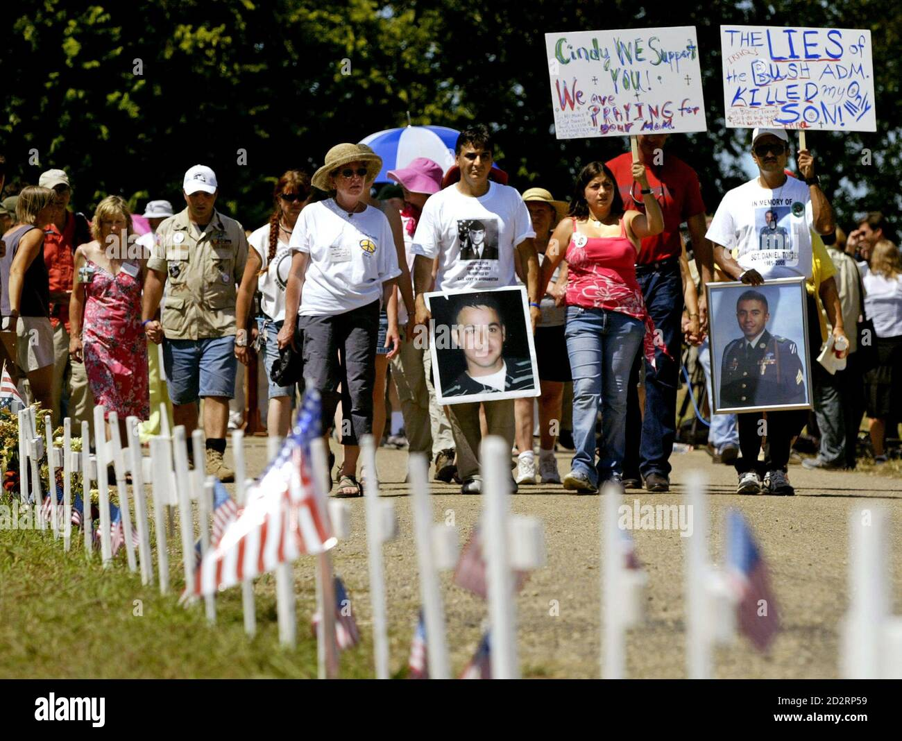 Anti-war protesters, led by Juan Torres (3rd R, front) who is carrying a picture of his military son, also named Juan, who was killed in Afghanistan, march past crosses representing dead U.S. soldiers near the ranch of U.S. President George W. Bush in Crawford, Texas August 19, 2005. In the absence of lead protester Cindy Sheehan, who raced back to California to visit her ailing mother, other parents of U.S. soldiers recently killed in the Middle East have rallied together for her cause, to meet with Bush in an effort to change his war policy. REUTERS/Jason Reed  JIR/CCK Stock Photo