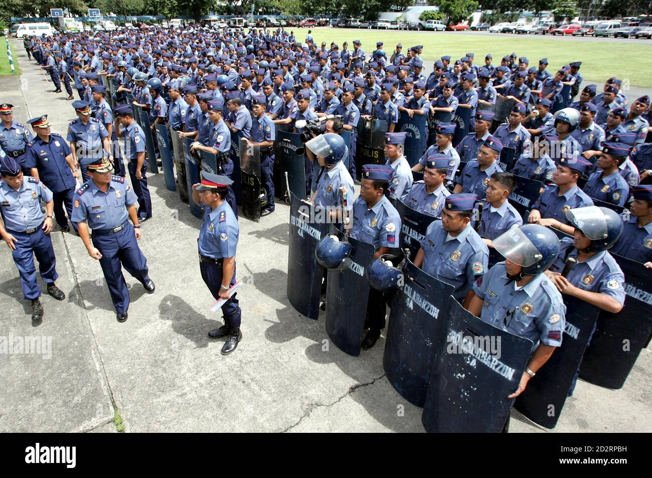 "Philippine police officers inspect anti-riot police at their headquarters in Manila's Quezon city September 21, 2005. Philippine security forces would no longer tolerate ""unlawful"" street protests, warning of a plot to unseat Philippine President Gloria Macapagal Arroyo as thousands marched to demand her resignation on Wednesday. REUTERS/Erik de Castro  EDC/CCK Stock Photo"