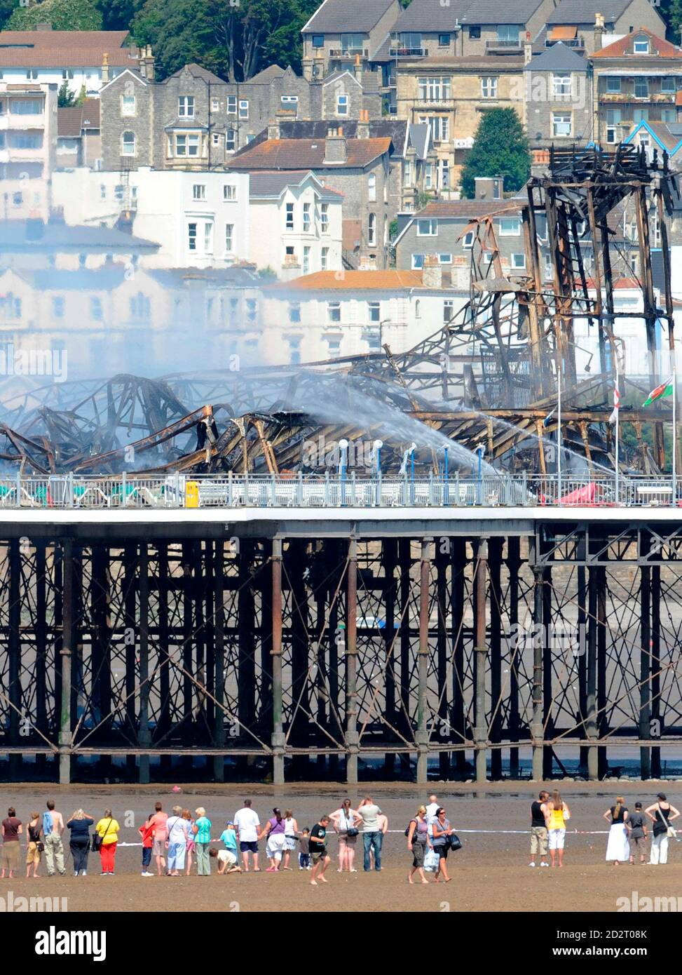 Holiday makers look at the Grand Pier at Weston-Super-Mare in south west England July 28, 2008. Firefighters were called to a large blaze that swept through the historic pier at the Somerset seaside resort of Weston-super-Mare on Monday, police said. Flames and thick black smoke engulfed the structure and could be seen from the M5 motorway, several miles from the coast, a fire brigade spokeswoman said.   REUTERS/Toby Melville    (BRITAIN) Stock Photo