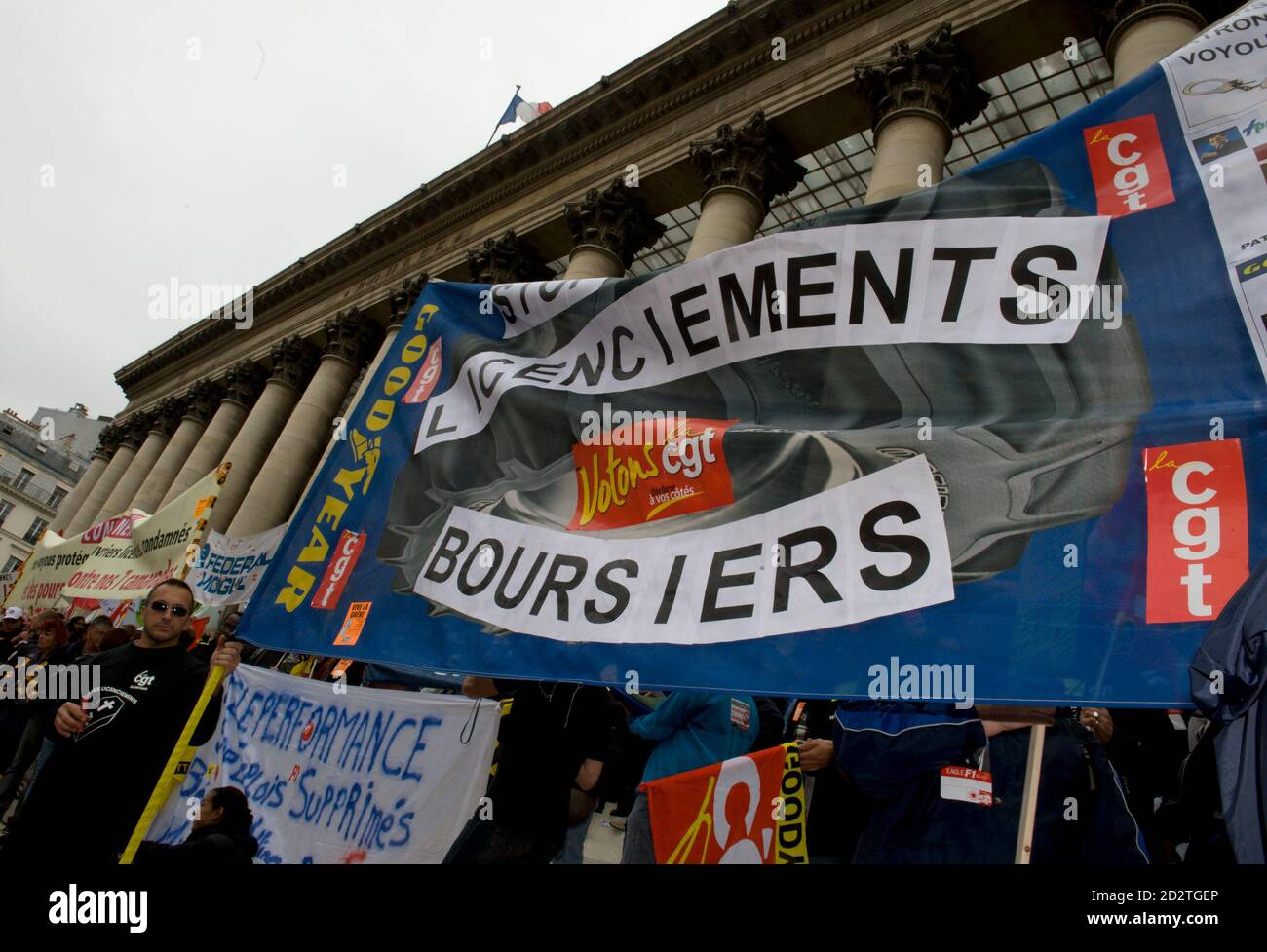 "Continental tyre workers and members of the automobile sector stand near a banner which partially reads, ""Stock Market Sackings"" outside the former Bourse (stock market) in central Paris, September 17, 2009. Continental's workers are protesting the announced closing of their factory at Clairoix, in northern France and its 1,120 workers have been fighting for guarantees for their future. REUTERS/Philippe Wojazer (FRANCE EMPLOYMENT BUSINESS CONFLICT) Stock Photo"