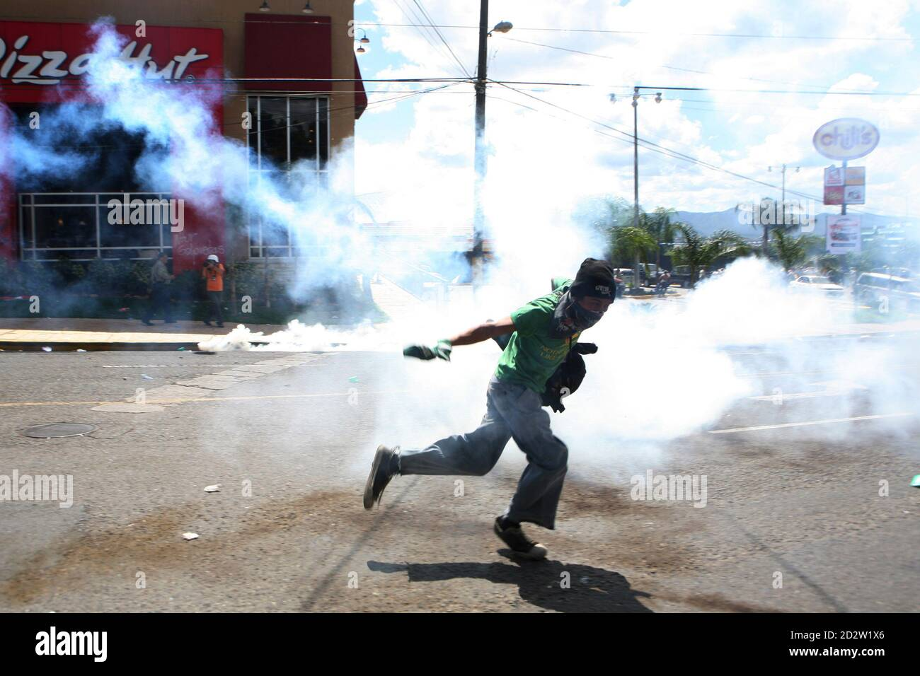 A supporter of Honduras' ousted President Manuel Zelaya kicks away a teargas canister during a protest near the site of negotiations to end the political crisis, in Tegucigalpa October 29, 2009. Zelaya and de facto rulers in power since a June coup returned to the negotiating table on Thursday, under pressure from U.S. officials who said time is running out to resolve the political crisis. REUTERS/Oswaldo Rivas (HONDURAS POLITICS CONFLICT) Stock Photo