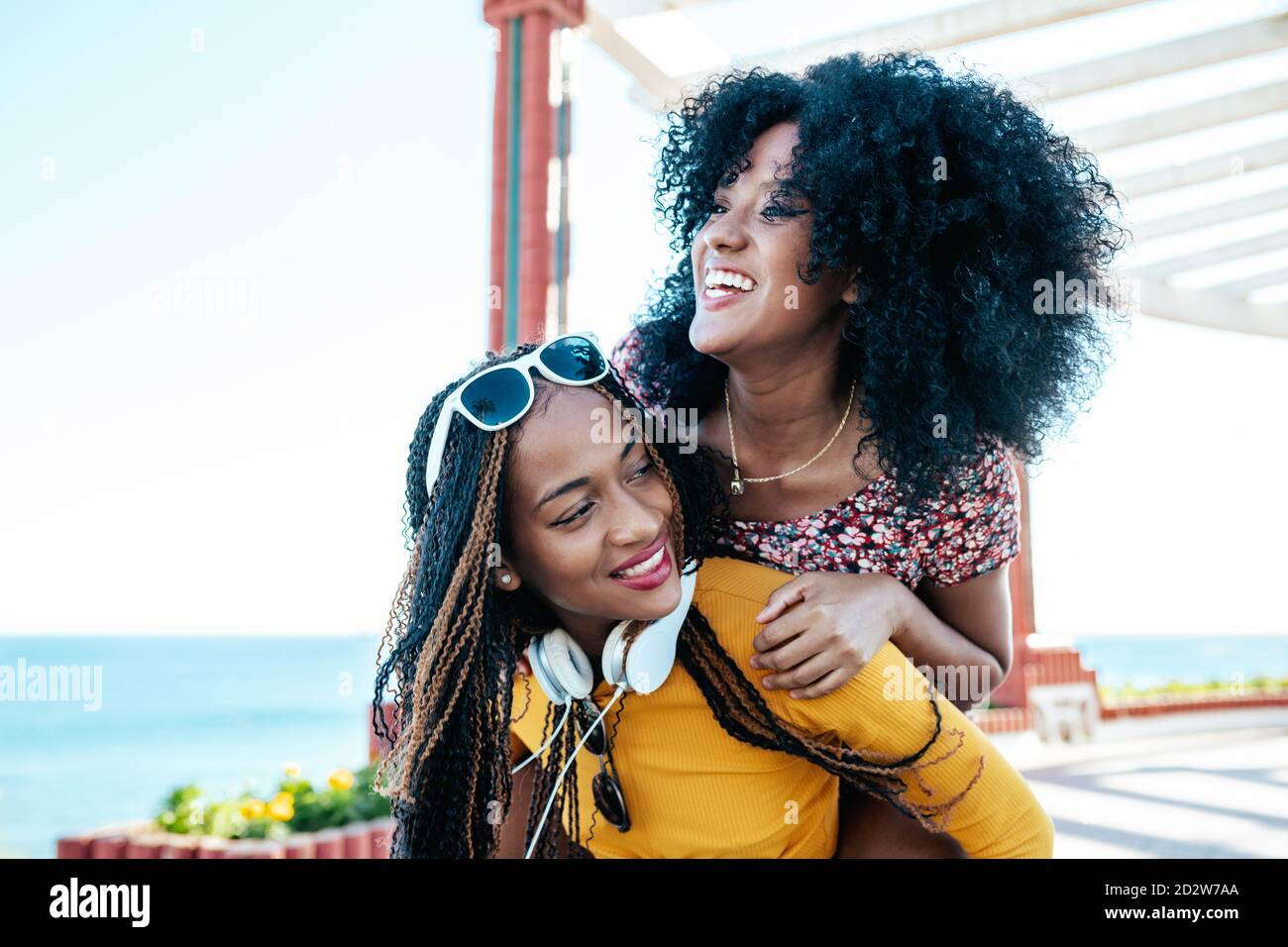 Cheerful ethnic woman with curly hair piggybacking delighted female friend with braids while having fun on promenade at weekend in summer Stock Photo