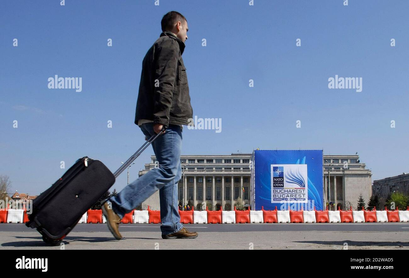 A man walks in Victoria square in front of a banner advertising upcoming NATO Summit during a rehearsal for traffic restrictions in Bucharest March 29, 2008. Romania's capital city Bucharest faces stringent security measures and traffic chaos during the April 2-4 NATO Summit. More than 30,000 personnel have been drafted to secure the bustling city and 6,500 delegates and journalists.  REUTERS/Bogdan Cristel (ROMANIA) Stock Photo