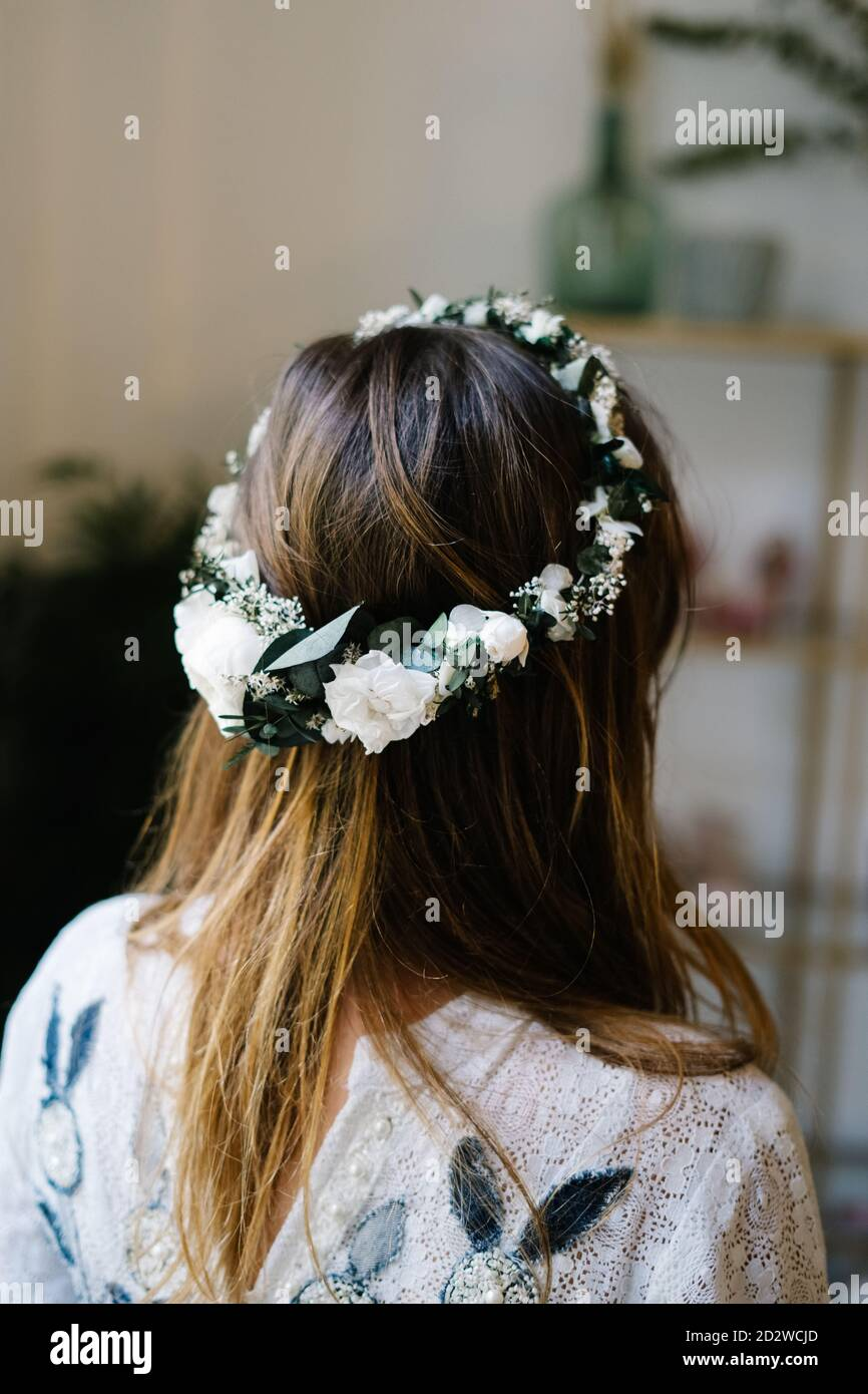 Back view of anonymous female wearing tender wreath with white rose flowers standing in flat Stock Photo