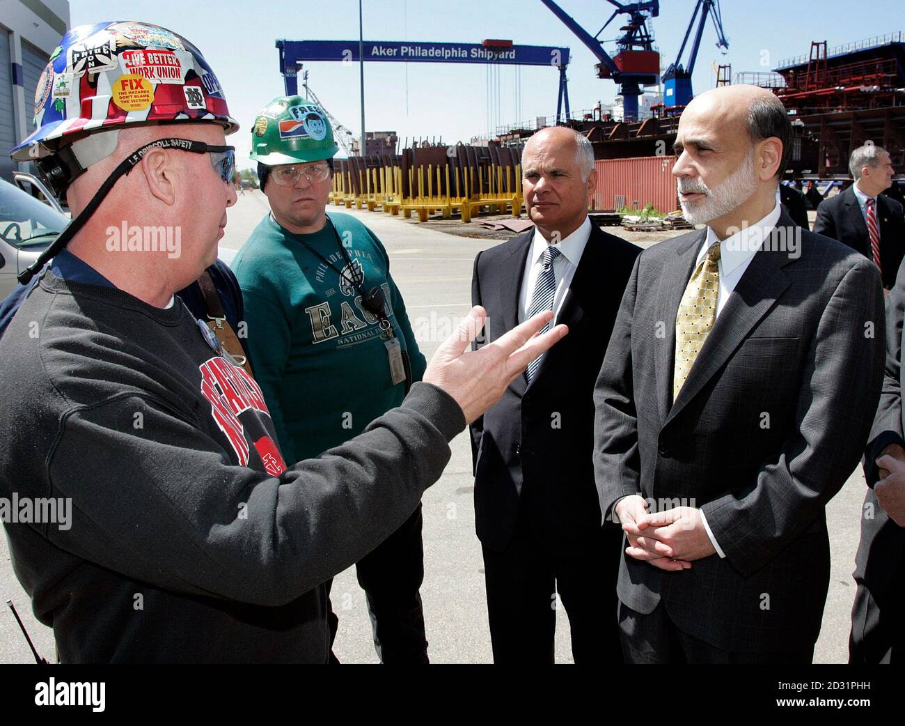 U.S. Federal Reserve Chairman Benjamin Bernanke (R) listens to Gary Gaydosh (L) describe the economic benefits brought by the Aker Philadelphia Shipyard to the regional economy during a tour of the shipyard in Philadelphia, Pennsylvania May 13, 2010. Looking on are Fred Chamerlain, (2nd L) and Charles Pizzi (2nd R), Chairman, federal reserve bank of Philadelphia, Board of Director.  REUTERS/Tom Mihalek (United States - Tags: BUSINESS POLITICS) Stock Photo