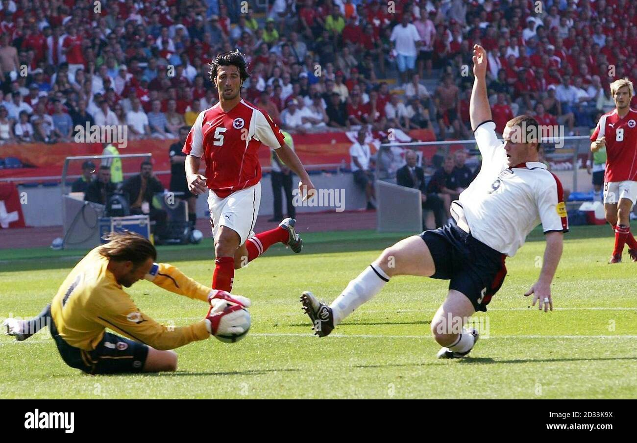 England's Wayne Rooney (right) challenges Switzerland goalkeeper Jorg Stiel, for which he later received a yellow card, during the Euro 2004, first round, Group B match at the Cidade de Coimbra, Portugal.   EDITORIAL USE ONLY, NO MOBILE PHONE OR PDA USE. INTERNET USE ONLY ON UEFA AUTHORISED SITES AND THEN, NO MORE THAN 10 PHOTOGRAPHS PER HALF OF NORMAL PLAYING TIME AND FIVE PHOTOGRAPHS PER HALF OF EXTRA TIME CAN BE PUBLISHED VIA THE INTERNET WITH AN INTERVAL OF AT LEAST ONE MINUTE BETWEEN THE POSTING OF EACH SUCH PHOTOGRAPH.    Stock Photo