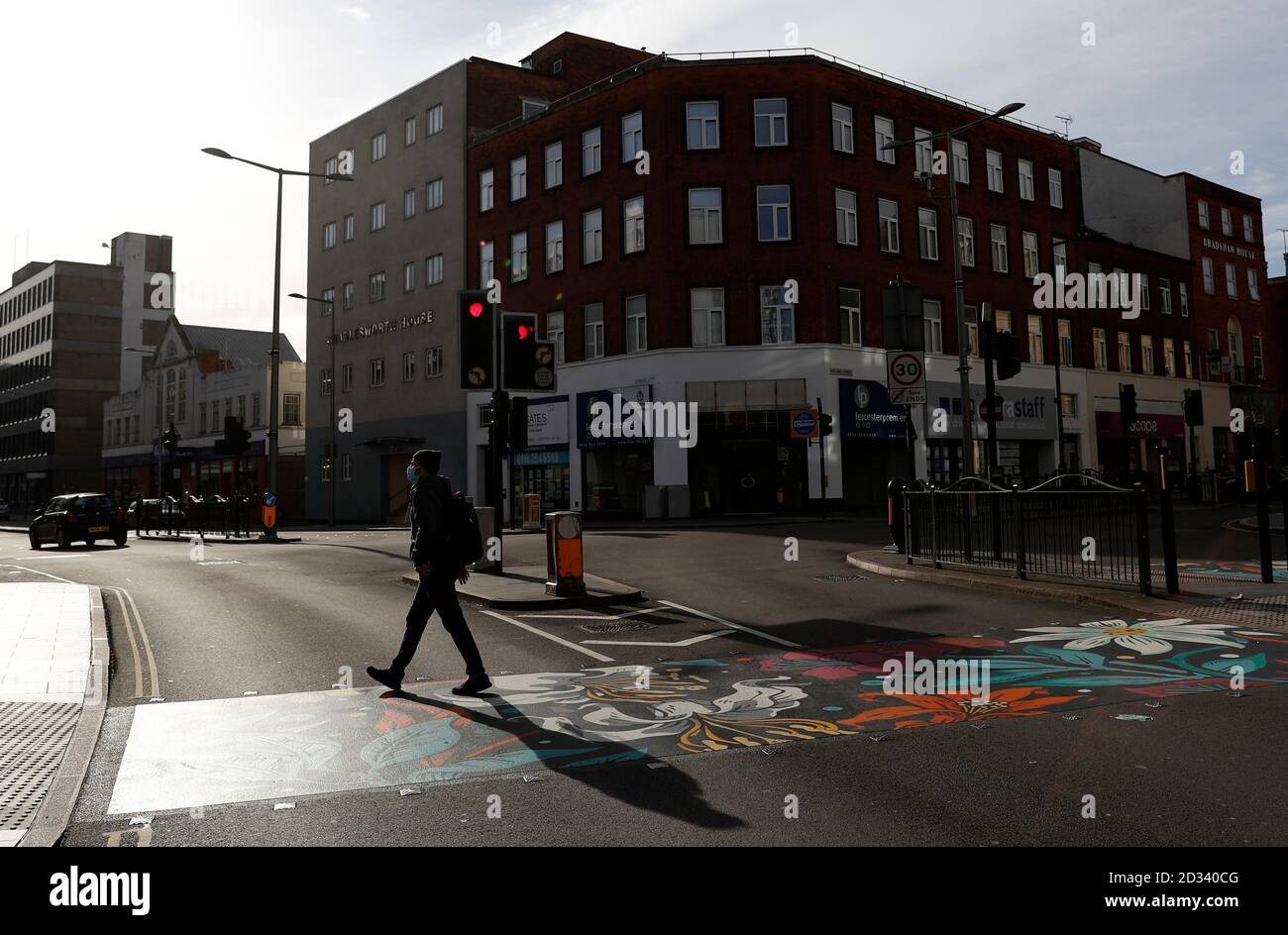 Leicester, Leicestershire, UK. 7th October 2020. A man walks on pedestrian crossing redesigned with colourful coverings 100 days since the UKÕs first local coronavirus pandemic lockdown was announced in the city. Credit Darren Staples/Alamy Live News. Stock Photo