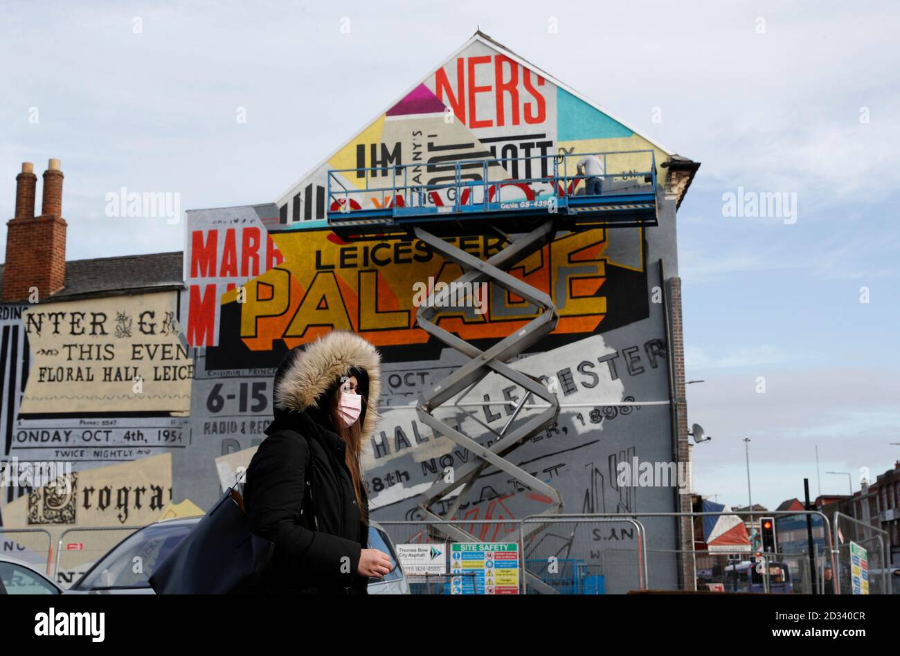 Leicester, Leicestershire, UK. 7th October 2020. A woman passes an artist working on a street mural 100 days since the UKÕs first local coronavirus pandemic lockdown was announced in the city. Credit Darren Staples/Alamy Live News. Stock Photo