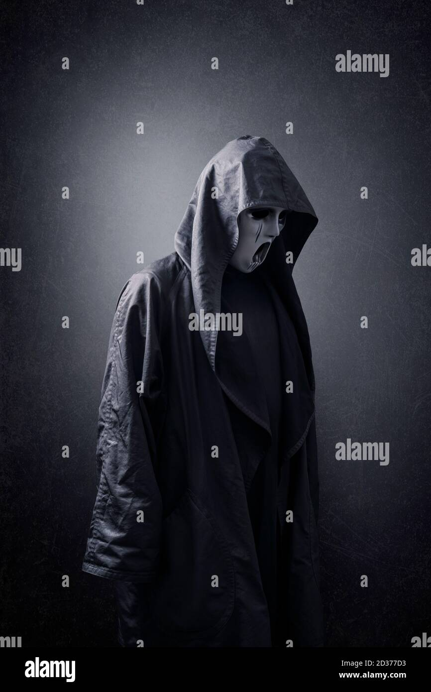 Scary figure with mask in hooded cloak in the dark Stock Photo