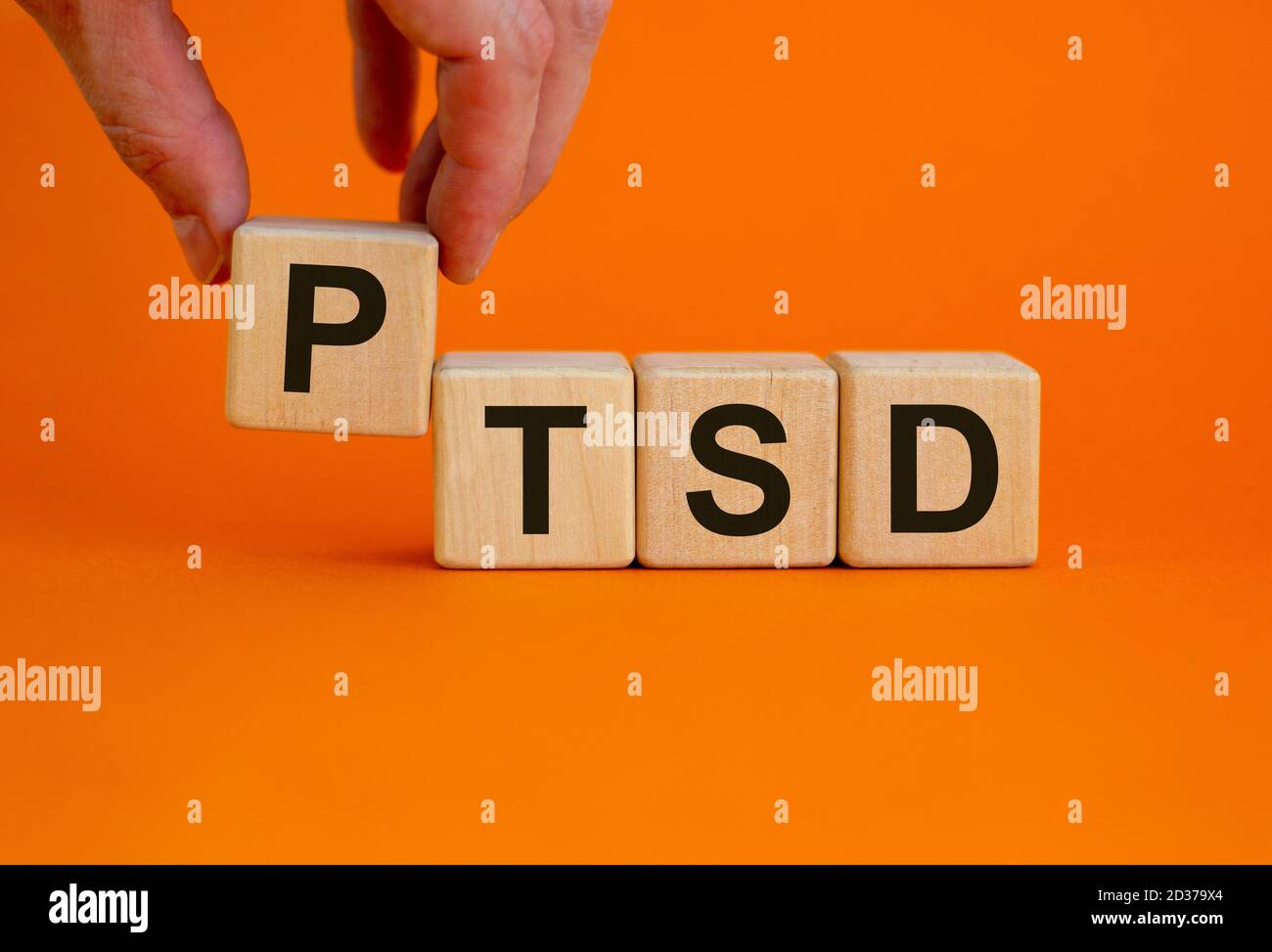 Concept words 'PTSD, post-traumatic stress disorder' on cubes on a beautiful orange background. Male hand. Copy space. Stock Photo