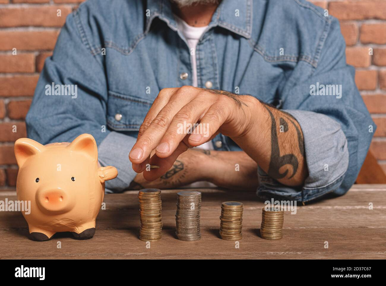 Hipster man stacks coins with a pig piggy bank on the table to save money and financial concept. Stock Photo
