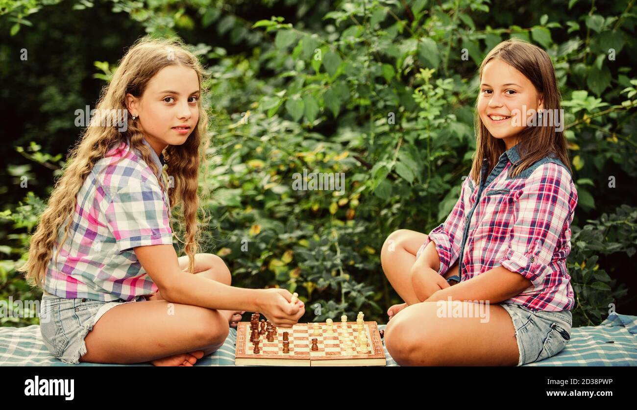 Cognitive development. Intellectual game. Make decision. Smart children. Little girls play chess. Sisters playing chess. Children play chess outdoors nature background. Sport and hobby concept. Stock Photo