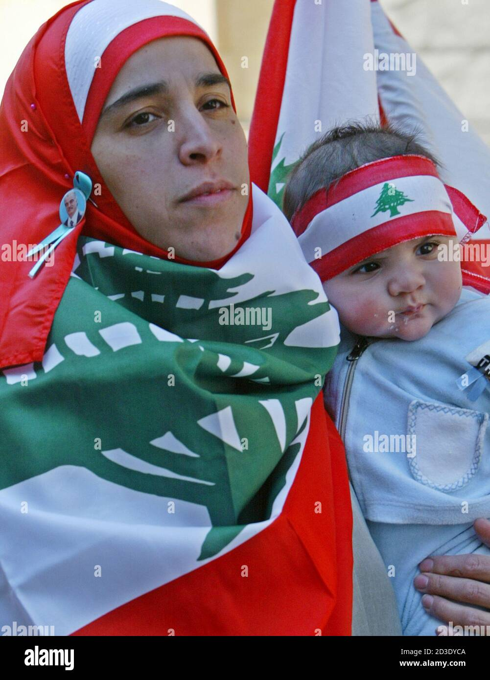 A woman, wrapped in Lebanon's national flag, carries her baby during an anti-Syrian rally in Beirut March 14, 2005. Hundreds of thousands of anti-Syrian protesters flooded central Beirut on Monday in what witnesses said was Lebanon's biggest demonstration since former prime minister Rafik al-Hariri's killing exactly a month ago. REUTERS/ Sharif Karim  JS/CCK Stock Photo