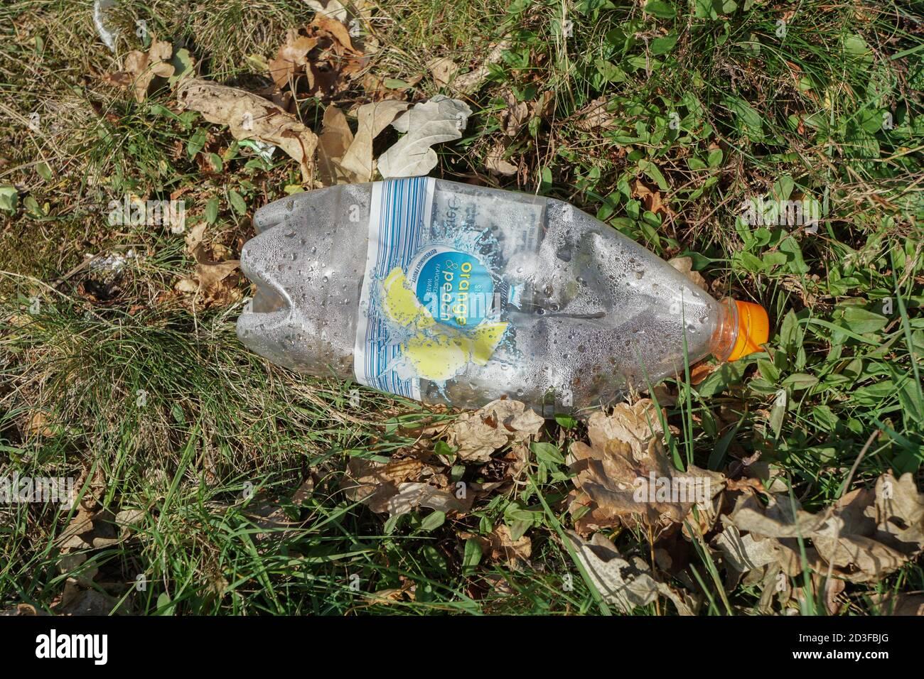 Discarde plastic drinks bottle on grass verge. England. UK Stock Photo