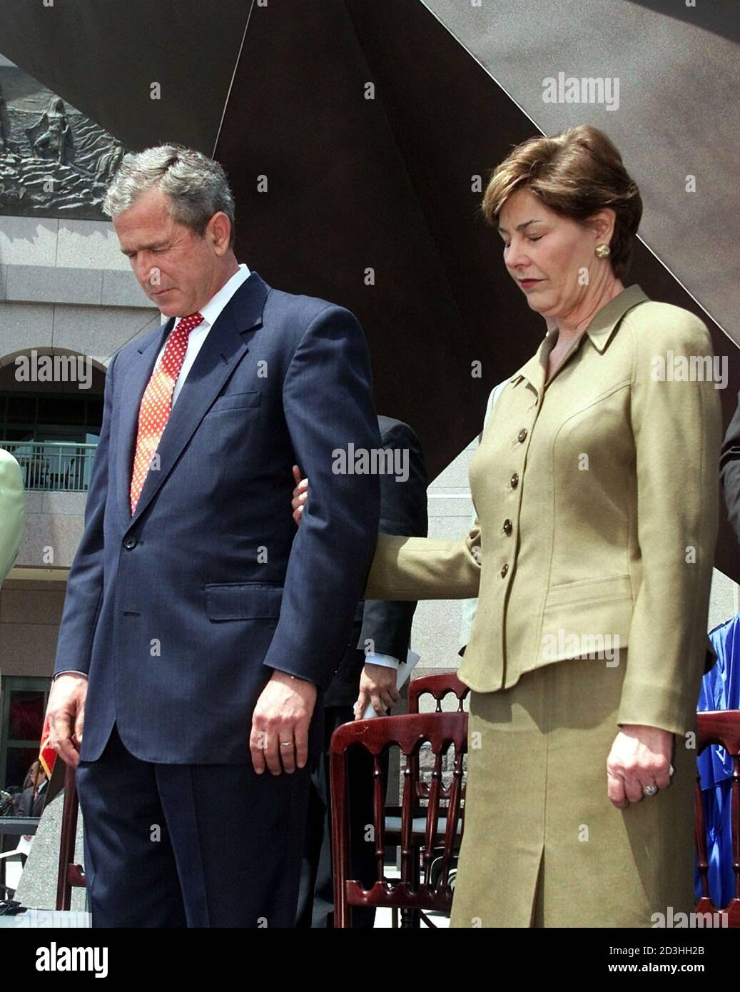 U.S. President George W. Bush and first lady Laura Bush bow their heads in prayer during the dedication of the Bob Bullock Texas History Museum while in Austin, Texas, April 27, 2001. The president is on a four-day swing through Louisiana, Arkansas and Texas promoting his administration's tax-relief package before returning to Washington this weekend.  LSD Stock Photo