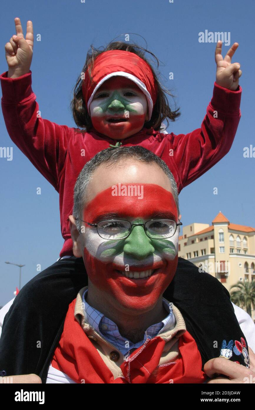 A man carries his son, their faces painted with Lebanon's national flag, during an anti-Syrian rally in Beirut March 14, 2005. Hundreds of thousands of anti-Syrian protesters flooded central Beirut on Monday in what witnesses said was Lebanon's biggest demonstration since former prime minister Rafik al-Hariri's killing exactly a month ago. REUTERS/ Sharif Karim  JS/CCK Stock Photo