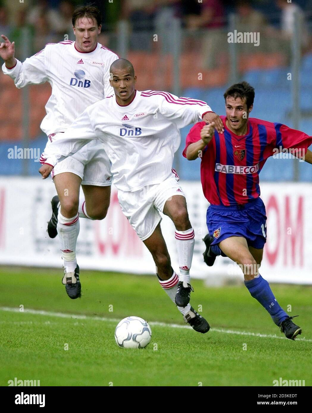 FC Basel's Sebastian Barberis (R) is held by Alex Valencia (M) of Norway's SK Brann Bergen as Thorstein Helstad (L) looks on during the UEFA Cup first round first leg match FC Basel vs. SK Brann Bergen in Zurich, Switzerland, September 12, 2000.  SIB/HM/JRE Stock Photo