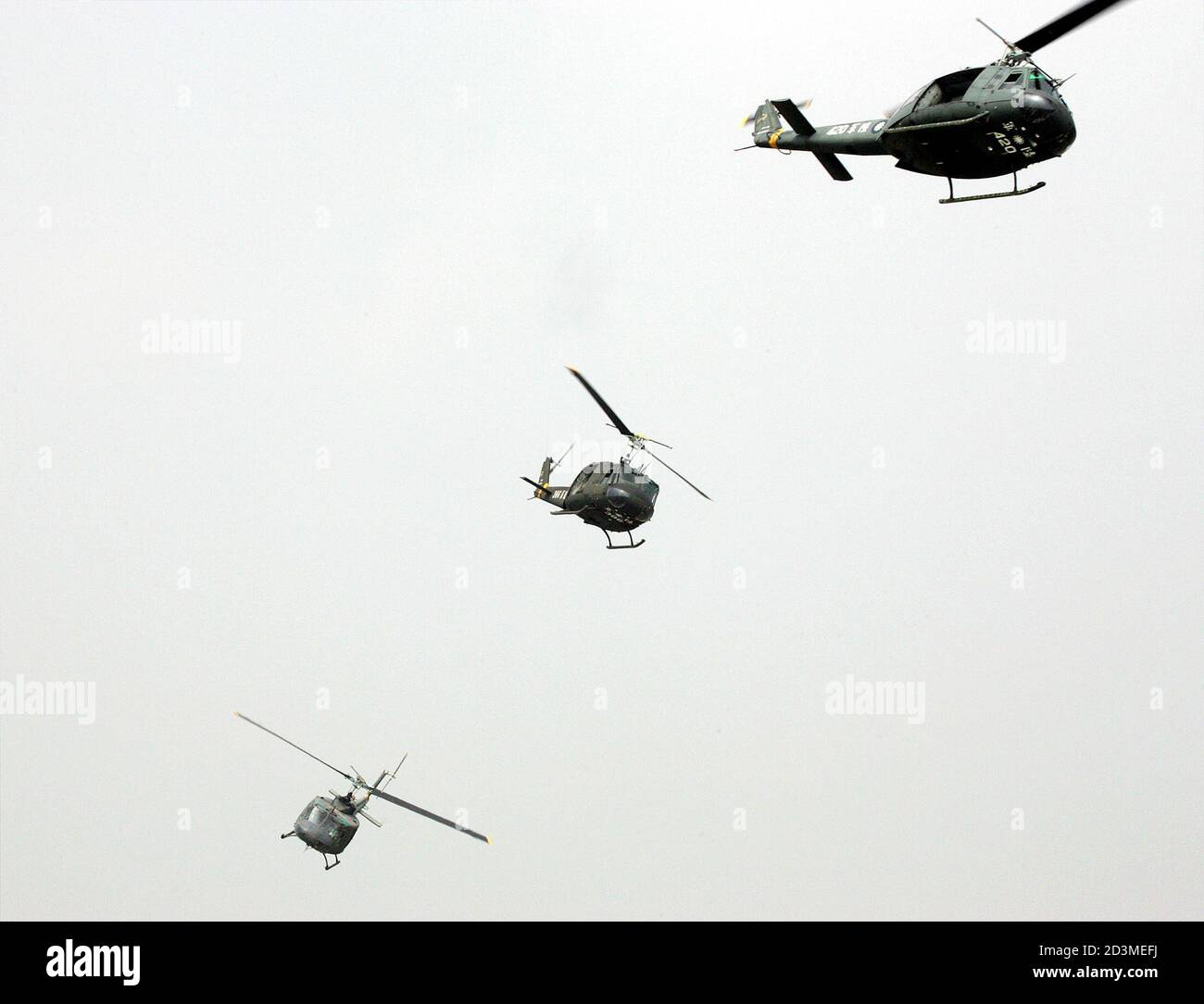 """Taiwanese helicopters simulate as Chinese enemies during anti-airborne exercise at CCK air base in Taichung.  Taiwanese helicopters simulate as Chinese enemies during an anti-airborne exercise at the CCK air base in Taichung, central Taiwan, July 27, 2005. The military exercise, involving simulated repulsion of airborne assaults on an airbase, is part of Taiwan's annual """"Han Kuang"""", or Chinese Glory, exercises aimed at testing the military's readiness against a Chinese invasion. Taiwan President Chen Shui-bian warned on Tuesday that arch-rival China's growing missile build-up not only posed a  Stock Photo"""