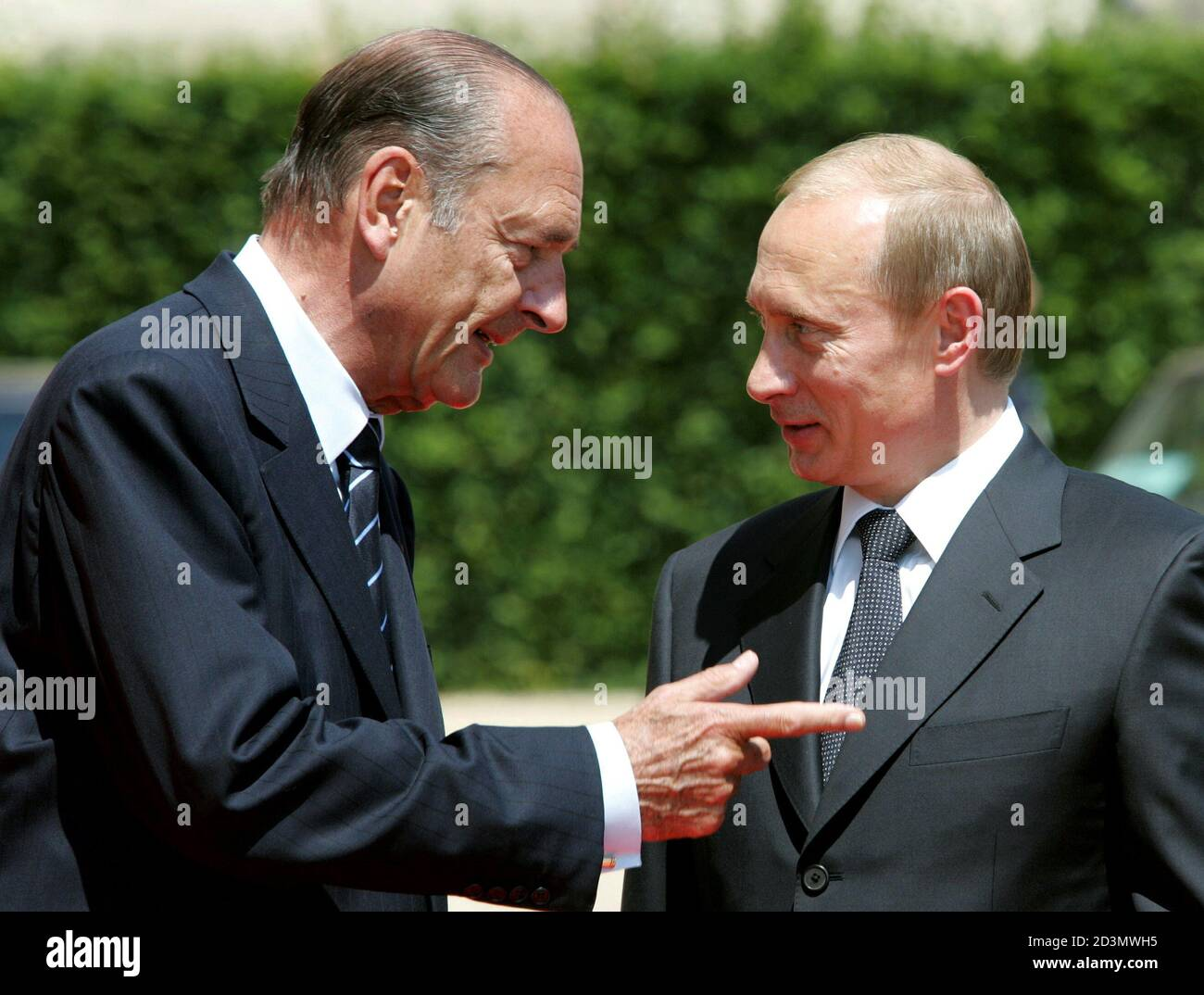 French President Jacques Chirac (L) points to Russian President Vladimir Putin (R) before a lunch at the Hotel de Ville in Caen, June, 6, 2004. [Putin is the first Russian leader to take part in D-Day events in France as veterans and World leaders gather for ceremonies celebrating the 60th anniversary of the Allied landing] in Normandy. Stock Photo