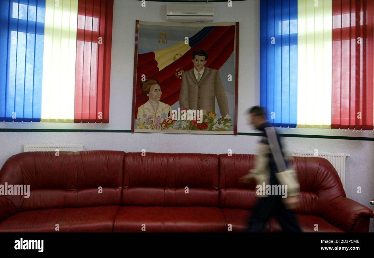 - PHOTO TAKEN 10NOV04 - A man walks in front of a portrait of Romania's late Stalinist dictator Nicolae Ceausescu and his wife Elena in the lobby of a hotel in a private park dedicated to the country's communist past near Craiova (250km west of Bucharest) in this November 10 file picture. Many in the impoverished countryside are nostalgic of Ceausescu ahead of Sunday's elections, saying they miss the job security they enjoyed during his time, and are expected to back the ruling socialists, successors of his communist party. Stock Photo