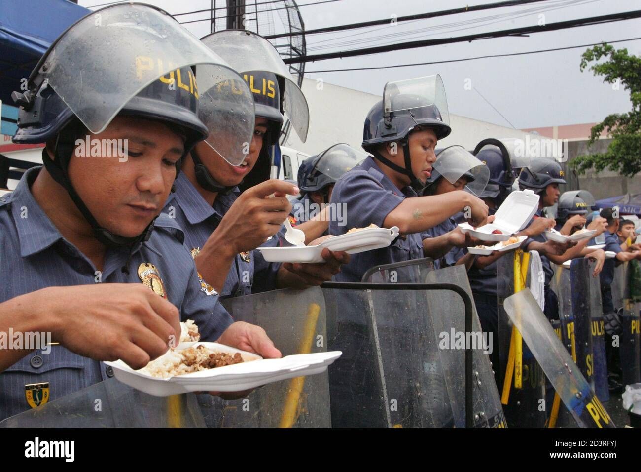 Filipino riot police take their lunch while blocking an anti-government protest march in the Manila suburb of Quezon City July 9, 2005. Philippine President Gloria Macapagal Arroyo could face judgment day on Saturday if the influential Catholic Bishops Conference of the Philippines joins the chorus calling for her to resign. Arroyo's political prognosis took a dramatic turn for the worse on Friday when, one by one, bastions of the establishment deserted her: cabinet ministers, corporate chieftains, civic groups and political allies. REUTERS/Claro Cortes IV  CC/CCK Stock Photo