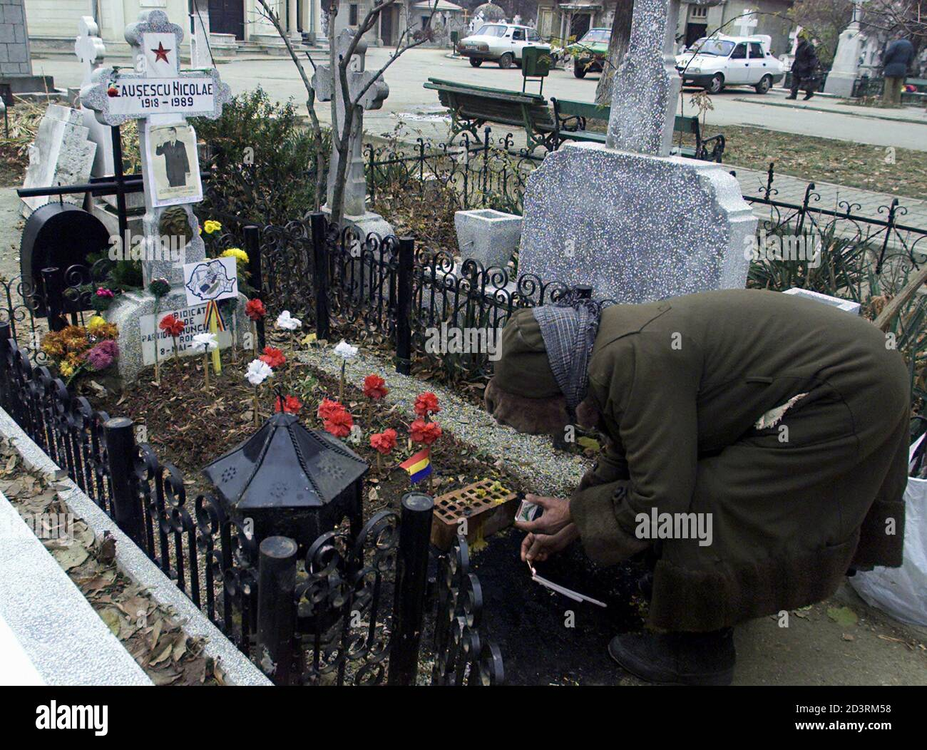 A Romanian woman lights candles at the grave where the late Stalinist dictator Nicolae Ceausescu is buried in a Bucharest cemetery after being shot on Christmas Day, 1989. Frustration with the slow pace of post-communist reform and the decline in living standards for many since the revolution has left a small minority longing for the return of the certainties of the Ceausescu era. Picture taken December 13, 2001. TO GO WITH FEATURE BC-ROMANIA-CEAUSESCU-EXECUTION. REUTERS/Bogdan Cristel REUTERS  BC/AA Stock Photo