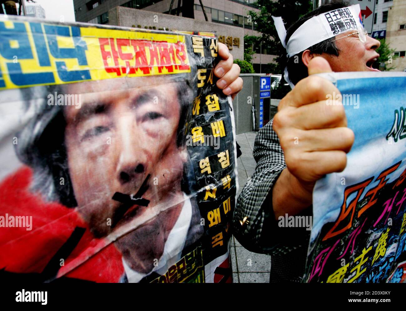 Protester shouts slogans at rally against Japanese Emperor Akihito's journey to pray for war dead in Seoul.  A South Korean protester shouts slogans with an anti-Japan banner featuring the portrait of Japanese Prime Minister Junichiro Koizumi at a rally against Japanese Emperor Akihito's journey to pray for war dead in Saipan, in front of the Japanese embassy in Seoul June 27, 2005. Japanese Emperor Akihito headed for the site of one of World War Two's most decisive battles on Monday to pay tribute to those who died in a conflict that still haunts Tokyo's ties with Asian neighbours, 60 years a Stock Photo