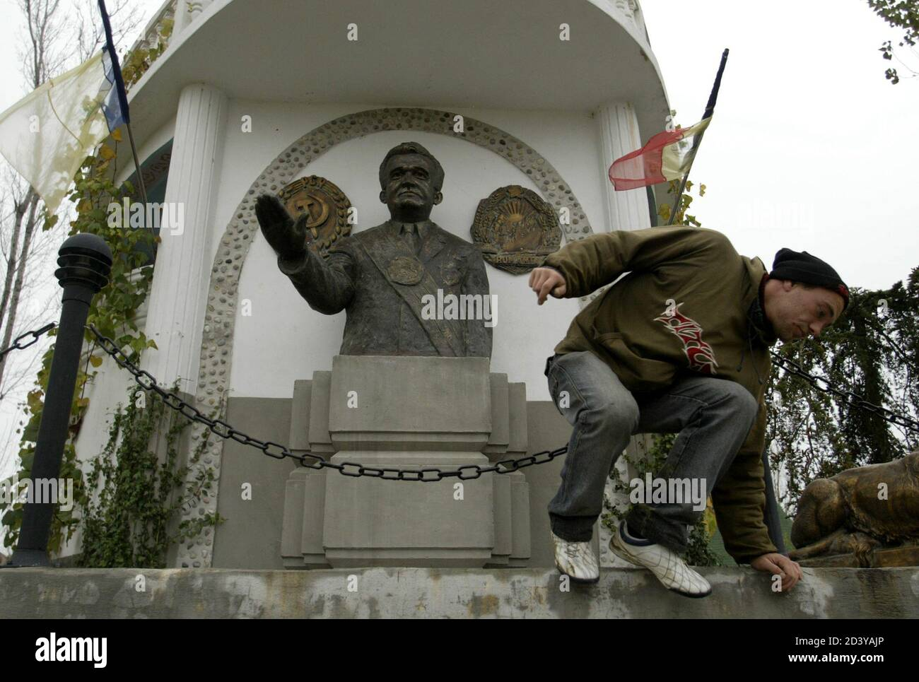 A workman jumps from a monument to Romania's late Stalinist dictator Ceausescu in a private park near Craiova.  A workman jumps from a monument to Romania's late Stalinist dictator Nicolae Ceausescu in a private park dedicated to the country's communist past near Craiova (250km west of Bucharest) in this November 10 file picture. Many in the impoverished countryside are nostalgic of Ceausescu ahead of Sunday's elections, saying they miss the job security they enjoyed during his time, and are expected to back the ruling socialists, successors of his communist party. TO GO WITH FEATURE BC-ROMANI Stock Photo