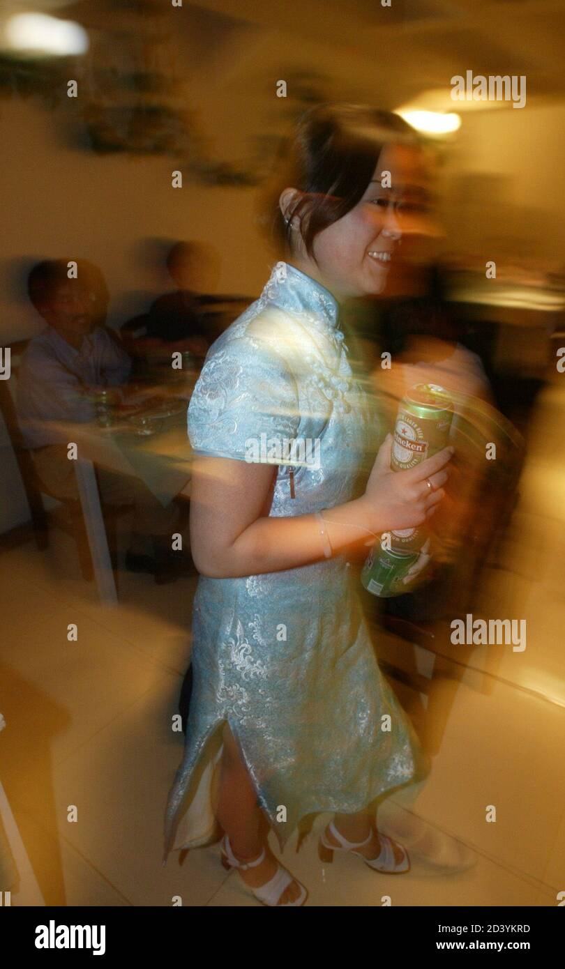 A waitress carries beer cans for customers at a chinese restaurant in Kabul, June 8, 2003. In Afghanistan,where the vast majority of Afghan women still wear burqa despite the Taliban having long gone, the westernised uniform of the waitresses show an increasing liberal side of the country. However, alcoholic drinks are served only to non-moslems. REUTERS//Arko Datta REUTERS  AD/ Stock Photo