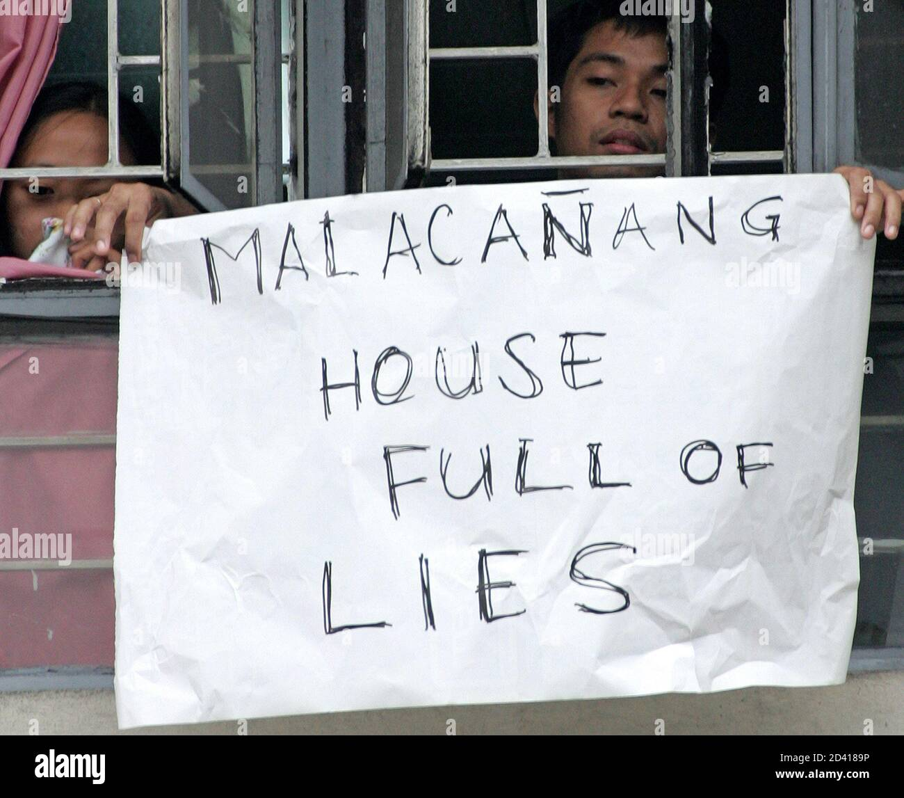 Filipino students display an anti-government sign from a school window during a protest demanding the resignation of Philippine President Gloria Macapagal Arroyo in Manila July 22, 2005. The Philippine opposition said on Friday it fears the government will try to scuttle its impeachment case against Arroyo and vowed more street protests if their bid to unseat her fails. REUTERS/Romeo Ranoco  RR/CCK Stock Photo