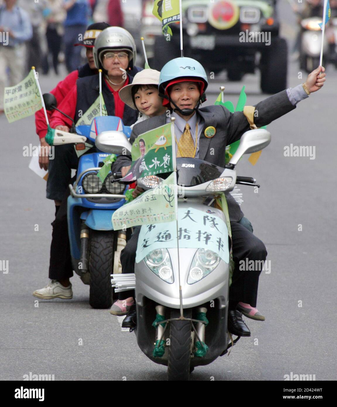 """Taiwan residents ride scooters and wave flags at a protest against China's anti-secession law in Taipei March 26, 2005. Hundreds of thousands of people chanting """"Oppose war, Love Taiwan"""" joined a protest against China's military threat in Taipei on Saturday. Organisers aimed to rally one million people in a show of people power against Beijing's anti-secession law, which sanctions the use of force against the island, but Taipei police estimated the crowd at just more than 230,000 so far. REUTERS/Richard Chung  TW/CCK Stock Photo"""