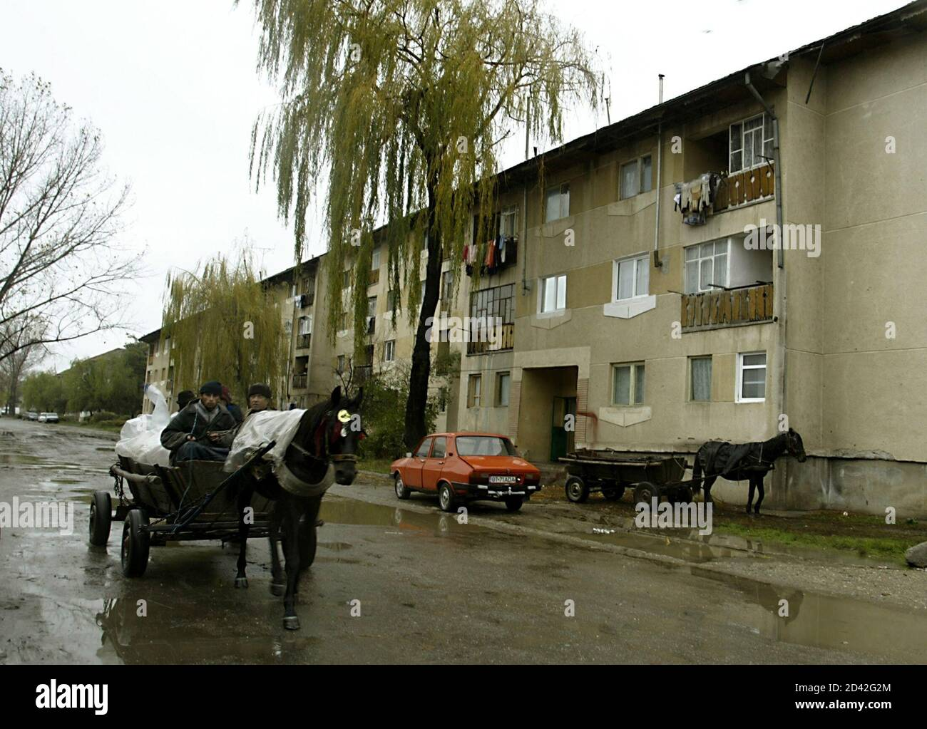 A horse-drawn cart passes by Communist apartment blocks lining a street in the town of Scornicesti (150km west of Bucharest), birthplace of the late Stalinist dictator Nicolae Ceausescu who tried to industrialise his home village, in this November 10, 2004 file picture. The urban-rural divide he tried to forcibly close by razing thousands of villages to the ground is a major factor in Sunday's elections, when impoverished peasants are expected to vote for the ruling socialists while urbanites for the more pro-business centrist opposition. TO GO WITH FEATURE BC-ROMANIA-ELECTIONS-DIVIDE. File pi Stock Photo
