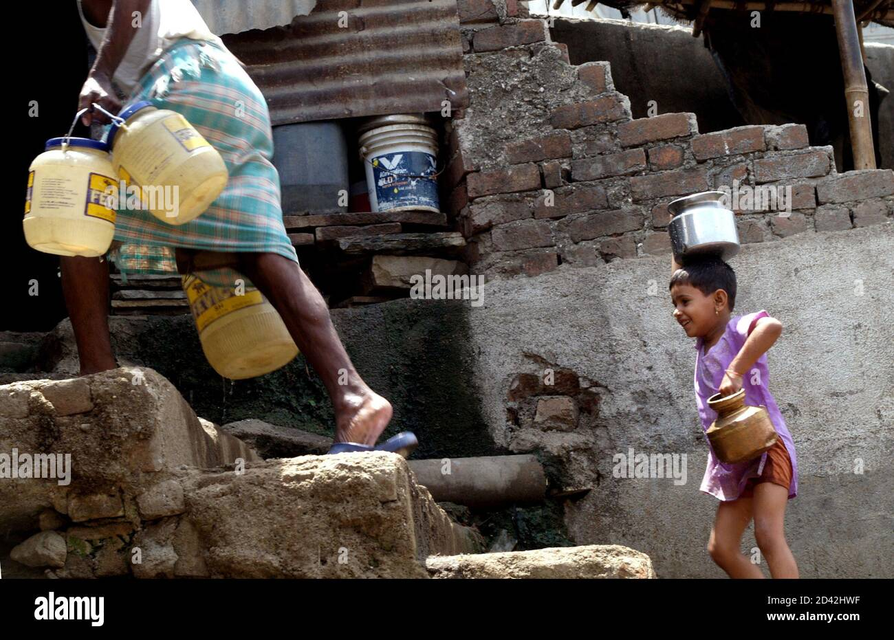 Kanika, a girl living in a slum, carries water pots home at a suburb in Bombay May 24, 2005. At present nearly 30 percent of Bombay's 18 million people live in slums without adequate supply of piped water. As more of them move into multi-storeyed buildings with piped water in every house, the demand for water is expected to skyrocket, according to the Indo-Asian News Service. REUTERS/Adeel Halim   AD/LA Stock Photo