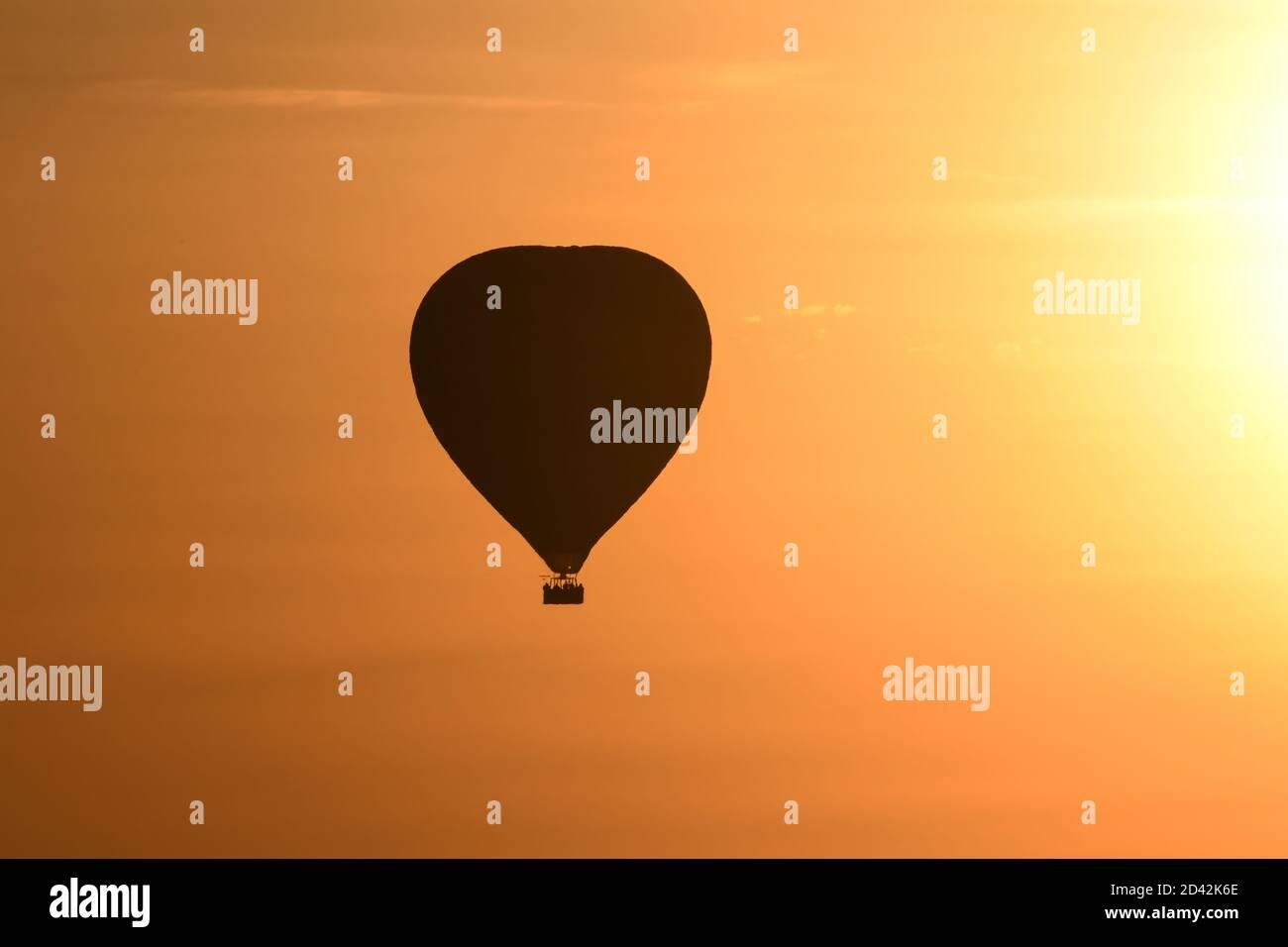 Silhouetted hot air balloon enjoying Serengeti Sunset in Kenya Stock Photo