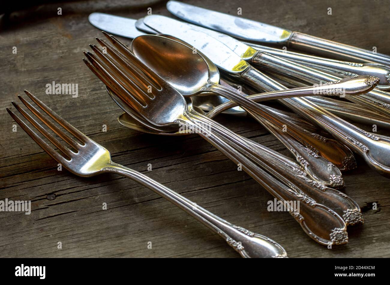 Fancy forks, knives and spoons are set out on a table, to be spread out for dinner Stock Photo