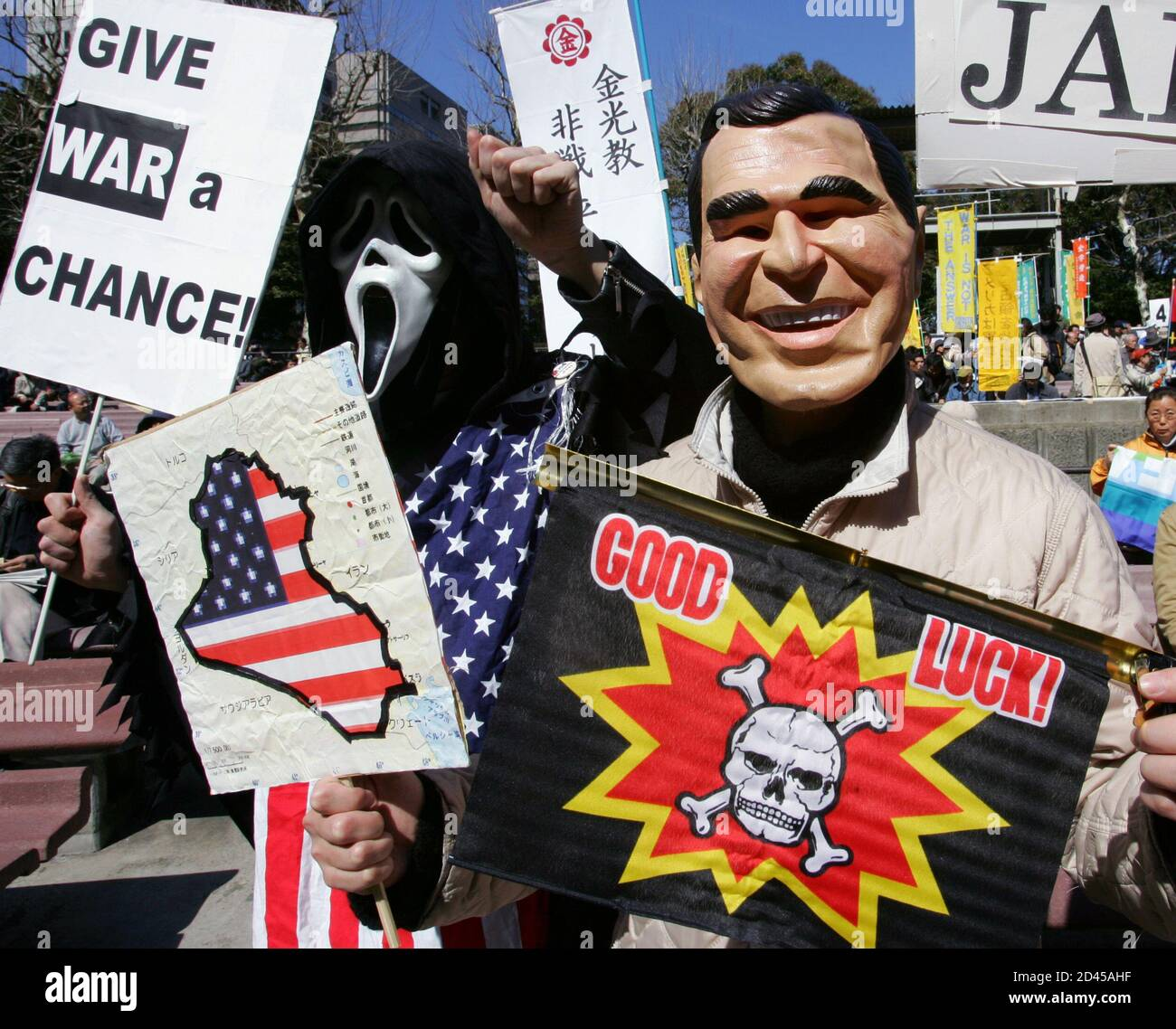 A protester (R) wearing a mask of U.S. President George W. Bush holds anti-U.S. placards as his fellow protester raises his fists during a rally in Tokyo March 19, 2005. March 20 marks the second anniversary of the U.S.-led war on Iraq. About 4,500 protesters gathered for the rally demanding the withdrawal of troops from Iraq, according to organisers. REUTERS/Issei Kato  IK/CCK Stock Photo
