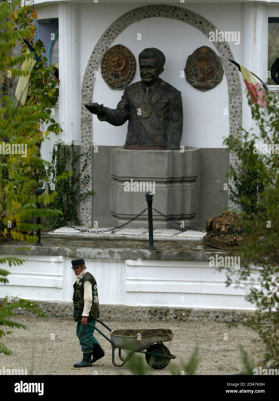 - PHOTO TAKEN 10NOV04 - A workman carries a cart past a monument to Romania's late Stalinist dictator Nicolae Ceausescu in a private park dedicated to the country's communist past near Craiova (250km west of Bucharest) in this November 10 file picture. Many in the impoverished countryside are nostalgic of Ceausescu ahead of Sunday's elections, saying they miss the job security they enjoyed during his time, and are expected to back the ruling socialists, successors of his communist party. Stock Photo