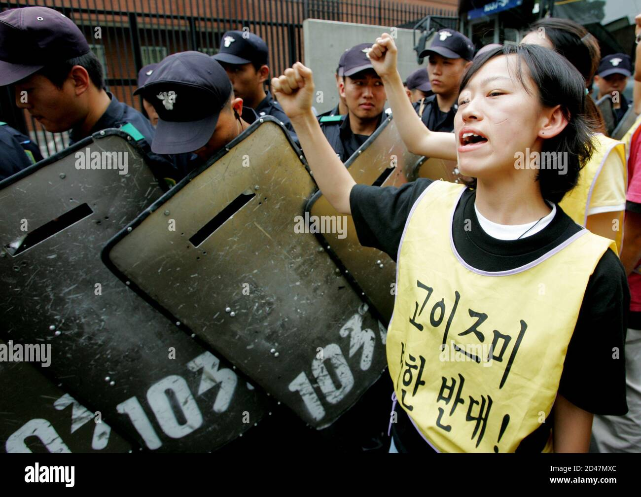 "South Korean riot police block protesters shouting slogans at an anti-Japan rally against Japanese Prime Minister Junichiro Koizumi's visit to South Korea in front of the Japanese embassy in Seoul June 15, 2005. Koizumi will try to mend fences when he meets South Korean President Roh Moo-hyun next Monday, but the summit is a gamble given the slim chances of improving frayed relations. The slogan in the vest reads ""Opposed to Japanese Prime Minister Junichiro Koizumi's visit to South Korea"". REUTERS/You Sung-Ho  KKH/CCK Stock Photo"
